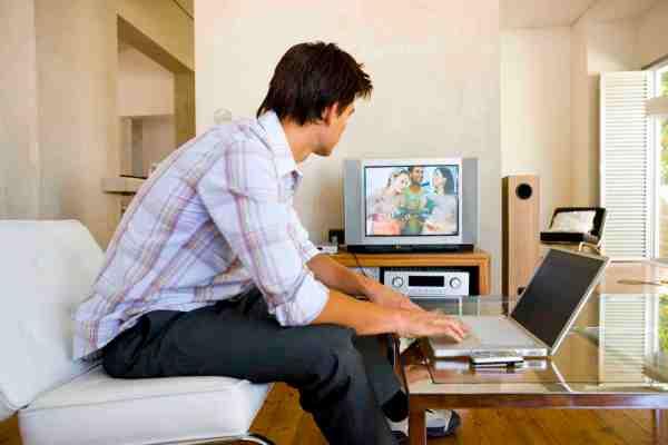 mezczyzna oglada telewizje i pracuje na laptopie
